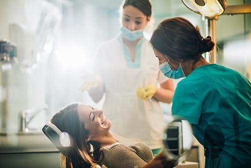 Smiling woman sitting in dentist chair and talking to her dentist before teeth examination.