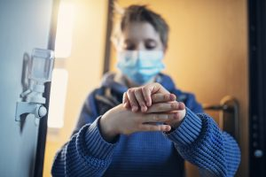 Little boy has returned from school during COVID-19 pandemic and is disinfecting his hands.