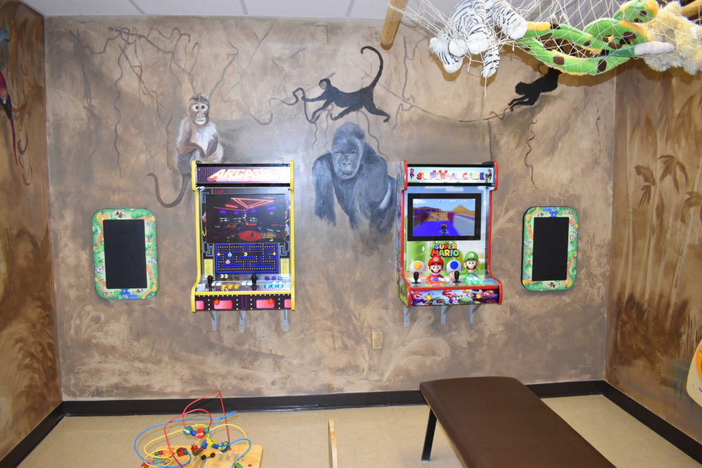 Kid Zone at PCCEK with monkeys, jungle animals, and video games on the wall